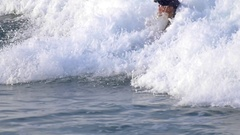 A young woman in a wetsuit surfing on a longboard surfboard, slow motion. Stock Footage