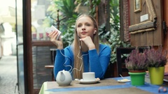 Girl looks relaxed while listening music in the cafe Stock Footage