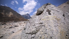 Orthodox cross on stone at Dingboche-Lobuche path. Lobuche peak is ahead Stock Footage