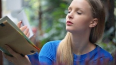 Girl receives message while reading book in the cafe, steadycam shot Stock Footage