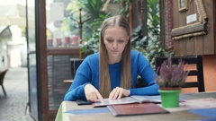 Girl receives message and texting back while reading menu Stock Footage