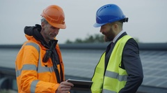 4K Businessman & engineer discussing operations at solar energy plant Stock Footage