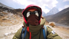 Man in sunglasses and warm clothes is making selfie while walking in mountains Stock Footage
