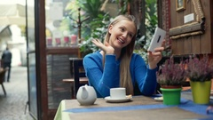 Happy girl sitting in the cafe and having a videocall on smartphone Stock Footage