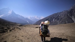 View of trekker's back with huge backpack on Dingboche-Lobuche path. Himalaya Stock Footage