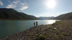 Couple strolling along bank of sunlit river holding hands, mountains on horizon Stock Footage