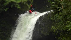 A man paddles his kayak down a waterfall on river rapids. Stock Footage