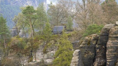 Cabin in the forest woods, rock formation in mountains, Bastei, Germany Stock Footage