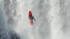 A man paddles his kayak down a waterfall on river rapids, slow motion. Stock Footage