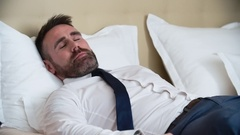 Businessman in Suit Sleeping in Bed Stock Footage
