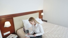 Businesswoman with Organizer on Hotel Bed Stock Footage