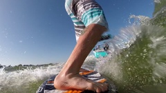 POV of a man's legs while wake surfing behind a boat on a lake. Stock Footage