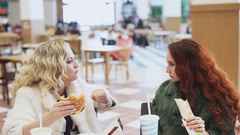 Two woman eating junk food Stock Footage