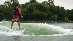 A man wake surfing behind a boat on a lake, slow motion. Stock Footage