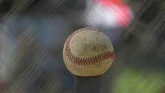 A boy hits a ball in a batting cage at little league baseball practice. Stock Footage