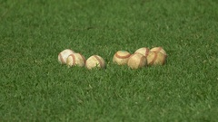 Hand-held focus racking shot of a group of baseballs on a green grass field. Stock Footage