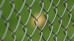 Hand-held focus racking shot of a baseball through a chain link fence on a green Stock Footage