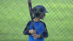 A boy hits a ball in a batting cage at little league baseball practice, slow mot Stock Footage