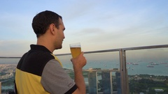 Male tourist drinking beer with view of Singapore Stock Footage