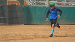 A boy runs to first base at little league baseball practice, slow motion. Stock Footage