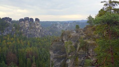 People on rock formations, fog mist clouds, lush green forest, Bastei, Germany Stock Footage