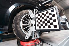 Car on stand with sensors wheels for alignment camber check in workshop of Stock Photos