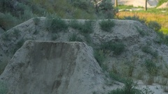 A bmx mountain biker does a back flip jumping trick on a dirt trail. Stock Footage
