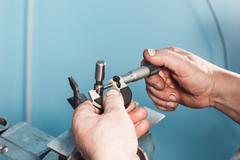 Mechanical technician worker hands measuring detail tool after processing at Stock Photos