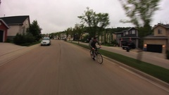 A mountain biker rides fast down a neighborhood road, slow motion. Stock Footage