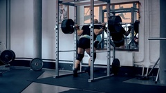 Male bodybuilder doing squats with a barbell at the gym Stock Footage