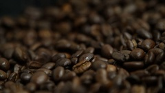 Coffee beans strewing onto the black background Stock Footage