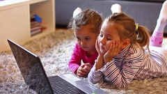 Two little girls with laptop at home Stock Footage
