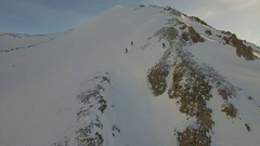 Aerial shot of young men snowboarding from the top of a mountain. Stock Footage
