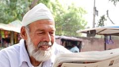 Bearded senior muslim reading newspaper Stock Footage