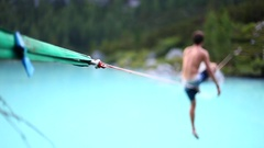 A man tries to balance while slacklining on a tightrope and walking over a lake. Stock Footage