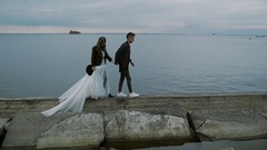 Beautiful stylish couple bride and groom walking along the embankment at dusk Stock Footage