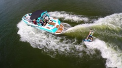 Aerial shot of a man wakeboard wake surfing behind a boat on a lake. Stock Footage