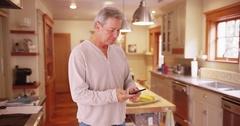 Beautiful Caucasian senior couple standing in house kitchen talking Stock Footage
