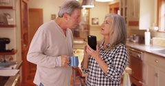 Portrait of a mature white couple looking at a cellular phone Stock Footage