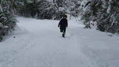 A boy running on snow-covered road in the winter forest and falls, Slow motion Arkistovideo