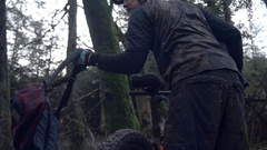 A man wearing a backpack goes mountain biking in the woods, super slow motion. Stock Footage