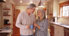 Lovely senior couple smiling, standing inside house kitchen Stock Footage