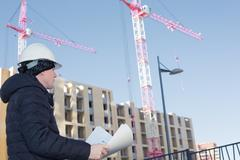 An engineer on a construction site with cranes and blueprints in hands Stock Photos