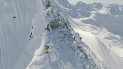 Aerial shot of skiers skiing from the top of a mountain. Stock Footage