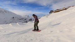 A snowboarder goes through a terrain park at a ski resort. Stock Footage