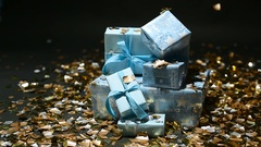 Gold confetti falling on blue gifts boxes Stock Footage