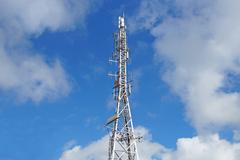 Telecommunication tower with antennas  blue sk Stock Photos