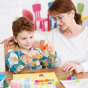 Occupational therapist and little boy Stock Photos