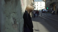 Beautiful blonde girl standing near the old wall in the city centre Stock Footage