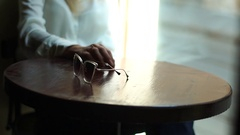 Sunglasses on the table against the Background of a Large Window in a Cafe Stock Footage